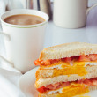 Sandwich with fried egg and tomatoes and cup of coffee — Stock Photo #71249601