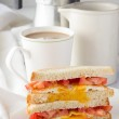 Sandwich with fried egg and tomatoes and cup of coffee — Stock Photo #71249609