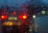 Blurry car silhouette seen through raindrops on the car windshie — Foto Stock