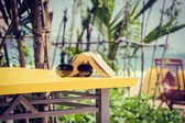Book and sunglasses lying on a yellow table in a tropical beach  — Stock Photo