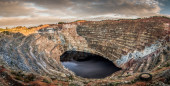 Panoramic an open pit mine with lake in the center — Stock Photo
