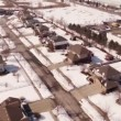 Aerial of homes in a snow covered suburban neighborhood — Stock Video #66030197