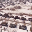 Aerial of homes in a snow covered suburban neighborhood — Stock Video #66030363