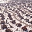 Aerial of homes in a snow covered suburban neighborhood — Stock Video #66030393