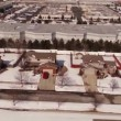 Aerial of homes in a snow covered suburban neighborhood — Stock Video #66030823