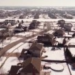 Aerial of homes in a snow covered suburban neighborhood — Stock Video #66031069