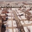 Aerial of homes in a snow covered suburban neighborhood — Stock Video #66031277