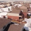 Aerial of homes in a snow covered suburban neighborhood — Stock Video #66031309