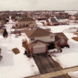 Aerial of homes in a snow covered suburban neighborhood — Stock Video #66313123