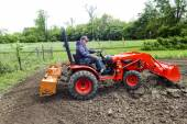 Older Farmer Tilling His Garden With A Small Tractor — Stock Photo