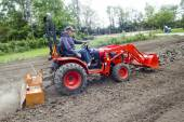 Older Farmer Tilling His Garden With A Compact 4x4 Tractor — Stock Photo
