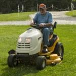 Senior Citizen Cutting Grass On A Riding Lawnmower — Stock Photo #76317157