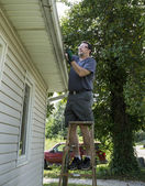 Worker Clearing Gutters Of Leaves & Sticks — Stock Photo