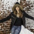 Girl in Furry Winter Hat Standing Against Brick Wall — Stock Photo #69639975