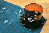 China cup and saucer on a blue embroidered napkins — Stockfoto