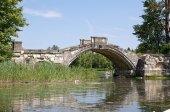 Stone bridge across a pond — Stock Photo