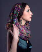 Beautiful young brunette woman in scarf — Stock Photo