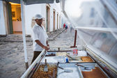 Man stands behind his food stall — Stock Photo