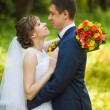 Happy bride, groom standing in green park, kissing, smiling, laughing — Stock Photo #66468227