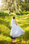 Beautiful bride on the wedding day standing in green park — Stock Photo