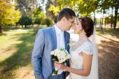 Happy bride, groom standing in green park — Stock Photo