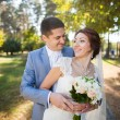Happy bride, groom standing in green park, kissing, smiling, laughing — Stock Photo #67171705