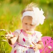 Beautiful carefree girl playing outdoors in field with high gree — Stock Photo #70320253