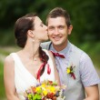 Happy couple standing in green park, kissing, smiling, laughing — Stock Photo #70355477