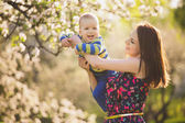 Little baby on hands of mother. woman playing with child outside — Stock Photo