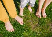 Happy family standing on grass in warm summer day — Stock Photo
