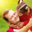 Little girl kissing her father on cheek while taking selfie — Stock Photo #77089703