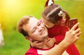 Little girl kissing her father on cheek while taking selfie — Stock Photo