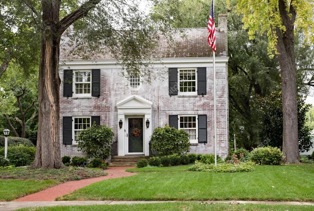 White Brick Georgian Colonial House With Flagpole Stock