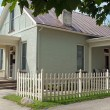 Corner Picket Fence with Small Stucco Cottage — Stock Photo #68268147