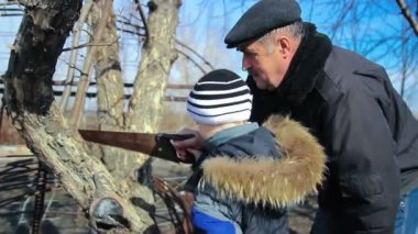 Grandfather and child with a saw working outdoors, 1080p HD video — Stock Video
