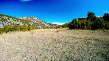 Young woman running on mountain trail in alpine pasture with mountain summits on the background — Vídeo de Stock