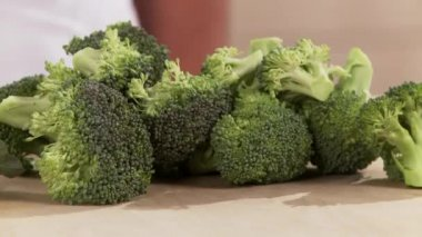 Broccoli florets and broccoli on table — Stock Video