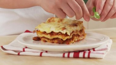 Lasagna being garnished with basil — Stock Video