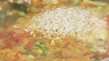 Risotto rice being added to minestrone — Stock Video