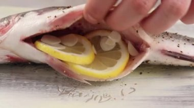 Bass being stuffed with basil — Stock Video