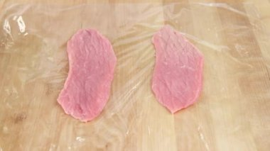 Escalopes being tenderized in cling film — Stock Video