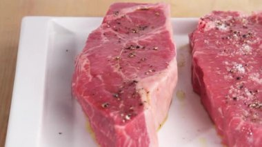 Steaks being seasoned with salt — Stock Video