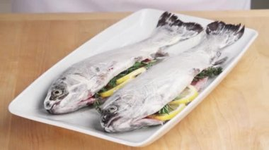 Prepared trouts being covered with cling film — Stock Video