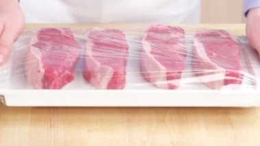Cling film being removed from steaks — Stock Video