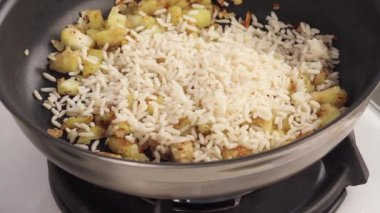 Rice being added to diced aubergine — Stock Video