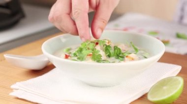 Coconut milk soup being garnished with herbs and chilli rings — Stock Video
