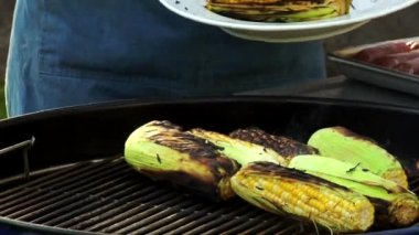 Man taking grilled corn on the cob — Stock video