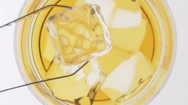 Putting ice into a glass of whisky — Stock Video