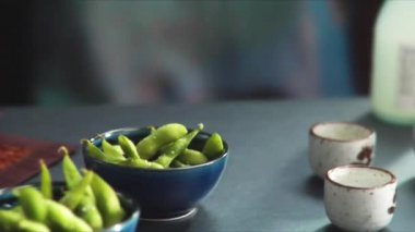 Sake beside steamed soya beans — Stockvideo