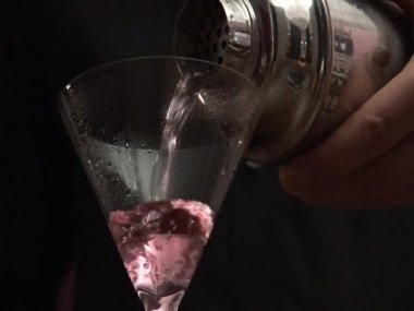 Bartender straining Cosmopolitan into a glass — Wideo stockowe